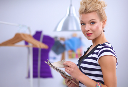attractive  female: Smiling fashion designer standing near mannequin in office isolated