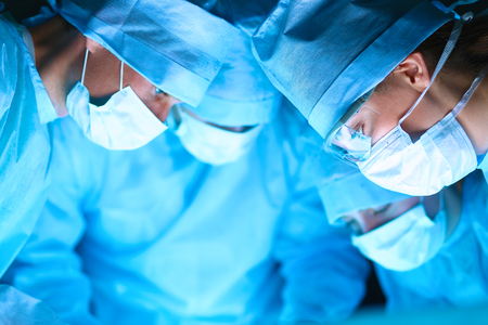 nurse gloves: Young surgery team in the operating room . Stock Photo