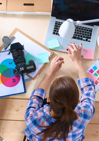 designer: Female photographer sitting on the desk with laptop . Stock Photo