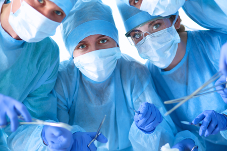 physicals: Below view of surgeons holding medical instruments in hands