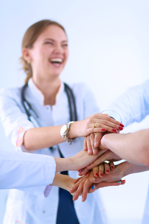 doctors smiling: Doctors and nurses in a medical team stacking hands