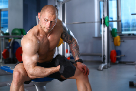 smiing: Young handsome man sits after workout in the gym .