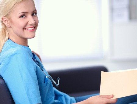 care worker: Closeup portrait of a happy young doctor sitting on the sofa with folder Stock Photo