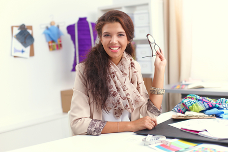 artists mannequin: Smiling female fashion designer sitting at office desk, isolated