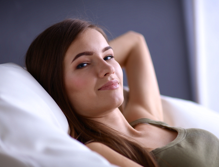Closeup of a smiling young woman lying on couch.
