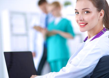 美しい若い笑顔女医、机に座っています。