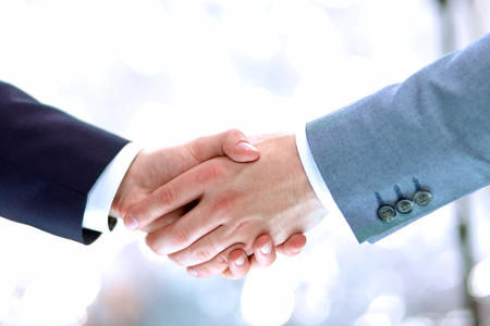 hand in hand: Businessmen shaking hands, isolated on white. Closeup