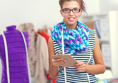working dress: Smiling fashion designer standing near mannequin in office isolated