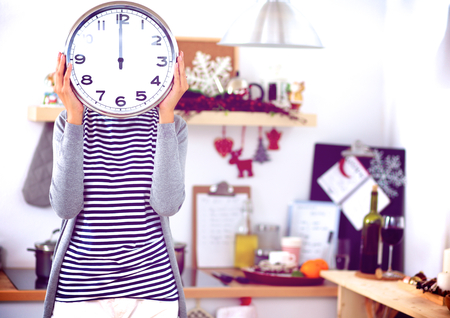 rest and relaxation: Young woman showing clock in christmas decorated kitchen