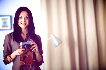 footage: Young woman watching footage on film, standing near window Stock Photo