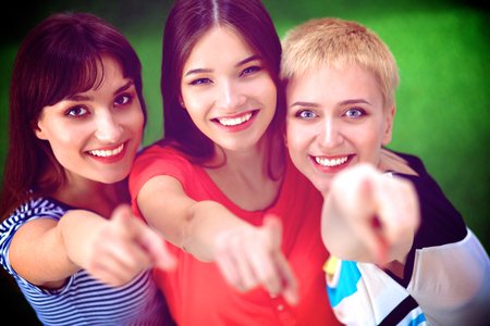 3 persons only: Portrait of three young women, standing together and pointing you.