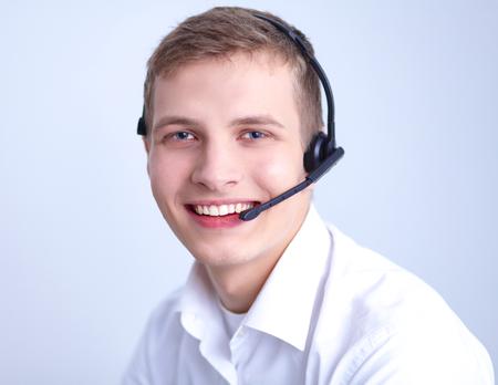 handsfree phone: Call center male operator on gray background