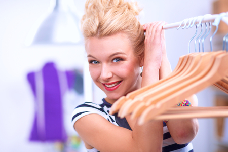 stylist: Beautiful young stylist near rack with hangers, isolated Stock Photo