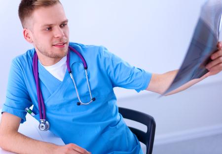 columna vertebral: Retrato de un doctor de sexo masculino con la imagen de rayos X de la columna vertebral Foto de archivo