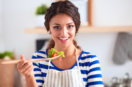 eating utensils: Young woman eating fresh salad in modern kitchen, isolated