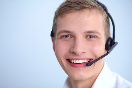 handsfree phones: Call center male operator on gray background