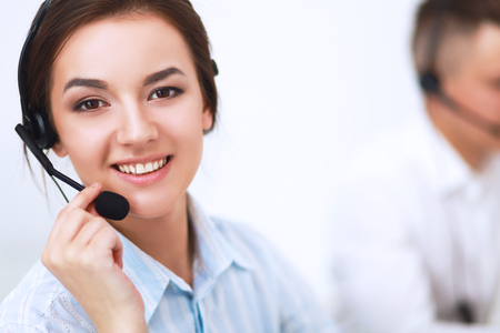 on call: Businesswoman with headset smiling at camera in call center atoffice Stock Photo