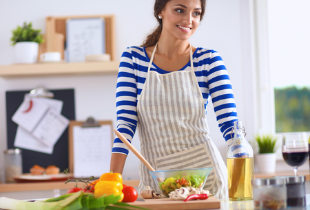 Smiling young woman  mixing fresh salad, standing