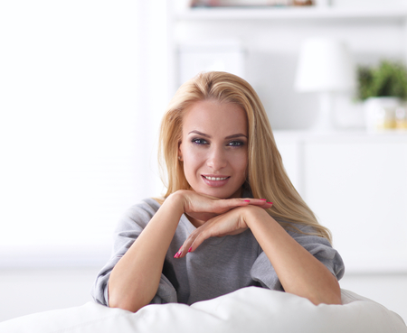 woman couch: Portrait of beautiful woman sitting on couch at her room