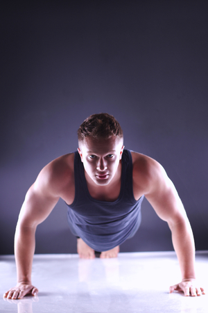 male body: Young fitness man doing push ups on floor, isolated on grey background Stock Photo