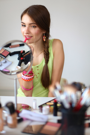making face: Young beautiful woman making make-up near mirror,sitting at the desk.
