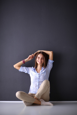 jeans skirt: Young woman sitting on the floor near dark wall.