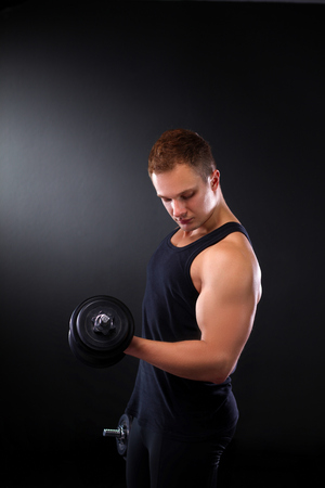 male body: Handsome muscular man working out with dumbbells.