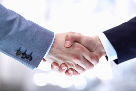 business hand shake: Businessmen shaking hands, isolated on white background.