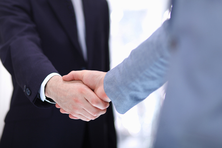 Businessmen shaking hands, isolated on white background.