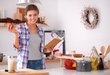 estilo de vida saludable: Mujer joven que lee libros de cocina en la cocina, en busca de la receta. Foto de archivo