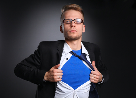 formal shirt: Young businessman acting like a super hero and tearing his shirt, isolated on gray background . Stock Photo