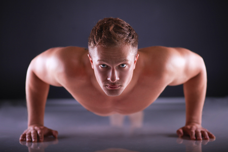 man power: Fitness man doing push ups on floor .
