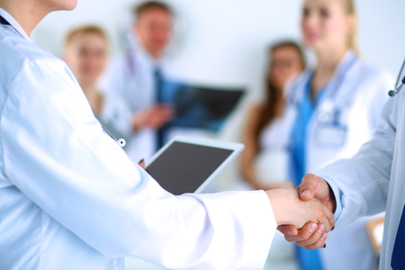doctor office: Young medical people handshaking at office .