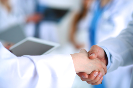 doctor woman: Young medical people handshaking at office .