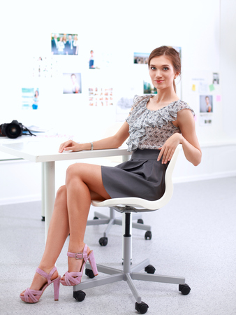 Attractive businesswoman sitting  in the office, isolated Stock Photo