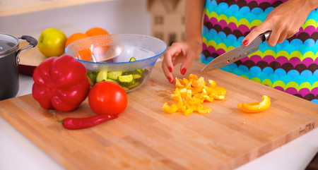 cutting vegetables: Young woman cutting vegetables in kitchen Stock Photo