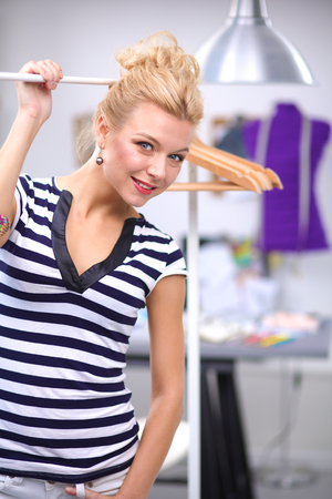 walk in closet: Beautiful young stylist near rack with hangers