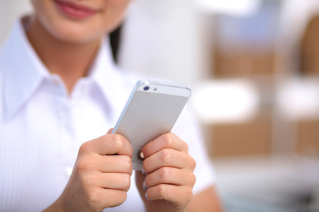 sending: Businesswoman sending message with smartphone in office