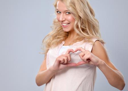 ragazza innamorata: Ragazza sorridente in camicia bianca mostrando cuore con le mani. Archivio Fotografico