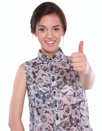 white achievement: Young woman showing thumb up, on gray background.