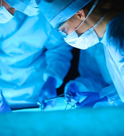 cirujano: Equipo de cirugía joven en la sala de operaciones. Foto de archivo