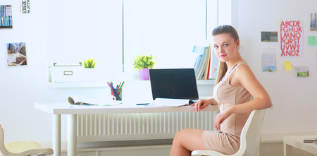confident business woman: Smiling woman with documents sitting on the desk with laptop