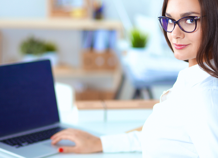 gleeful: Attractive businesswoman sitting  in the office, at the desk Stock Photo