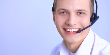 hands free phones: Call center male operator on gray background
