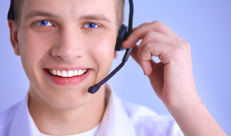 hands free device: Call center male operator on gray background