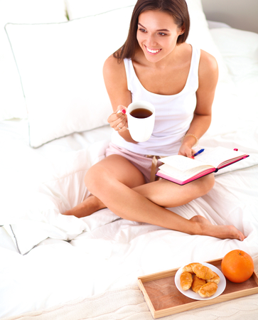 copybook: Young beautiful woman sitting in bed and writing in a copybook.