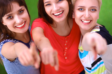 standing together: Portrait of three young women, standing together and pointing you.