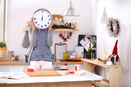 hour: Happy young woman showing clock in christmas decorated kitchen .