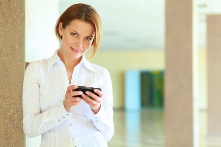 busineswoman: Portrait of young busineswoman standing with phone in office lobby?