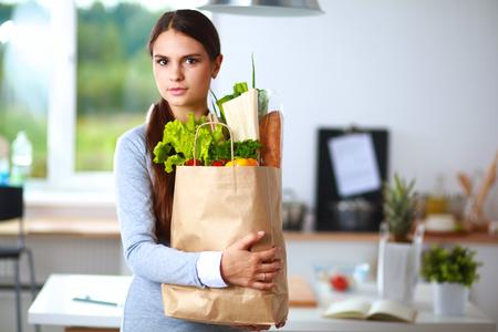 comiendo frutas: Mujer joven que sostiene la bolsa de compras con los vehículos. De pie en la cocina.